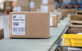 A brown cardboard box sits on a conveyor belt in a distribution warehouse. It has a priority mail label on it as well as a bar code and QR code.